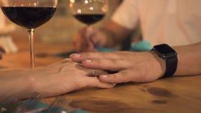 Mano masculina que toca la mano femenina mientras que fecha romántica en la igualación del restaurante Mujer que toca a la novia  metrajes