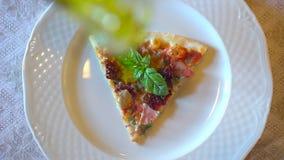 Mano masculina que vierte el aceite de oliva en la rebanada de pizza en restaurante o café Adición del aceite de oliva virginal a almacen de metraje de vídeo