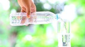 Mano masculina que vierte el agua limpia de la bebida almacen de video