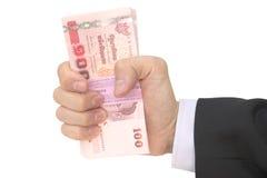 Mano masculina tailandesa que maneja el paquete de 100 billetes de banco Fotos de archivo libres de regalías