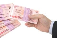 Mano masculina tailandesa que maneja el paquete de 100 billetes de banco del baht 100 con la pila de paquete de fondo de 100 bill Imagen de archivo