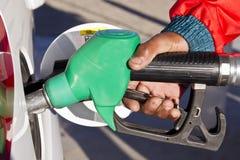 Mano masculina usando un surtidor de gasolina verde Fotografía de archivo libre de regalías