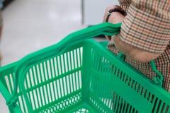 Mano mayor arrugada del ` s de la mujer que sostiene la cesta de compras en alameda de compras Atención sanitaria, ayuda, ayuda,  foto de archivo libre de regalías