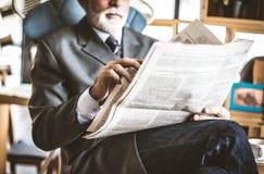 Mano mayor del hombre de negocios con los periódicos imagen de archivo