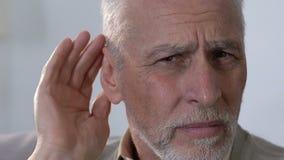 Mano mettente maschio anziana sull'orecchio, perdite della capacità uditiva, sordità, primo piano video d archivio