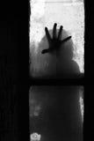 Mano misteriosa en una ventana Imagen de archivo libre de regalías