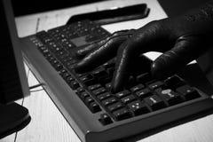 Mano nei tipi neri del guanto sulla tastiera Fotografia Stock Libera da Diritti