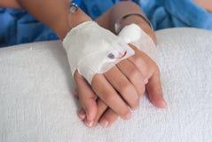 Mano paziente asiatica del ragazzo con il dispositivo di venipunzione salino (iv) sull'ospedale Fotografia Stock