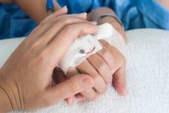 Mano paziente del ragazzo della tenuta con il dispositivo di venipunzione salino (iv) in hospita Fotografia Stock