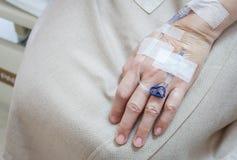 Mano paziente del ` s con il gocciolamento che riceve una soluzione salina Fotografia Stock Libera da Diritti
