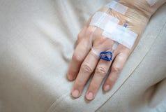 Mano paziente del ` s nell'ospedale con il gocciolamento salino del dispositivo di venipunzione del dispositivo di venipunzione Fotografia Stock Libera da Diritti
