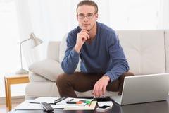 Mano pensativa del hombre en la barbilla usando la calculadora Fotos de archivo libres de regalías