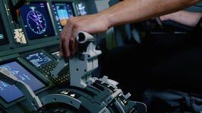 Mano pilota della tenuta sulla maniglia di leva di spinta per controllo di motore dell'aereo di linea fotografia stock libera da diritti