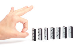 Mano pronta a spingere i domino Fotografia Stock