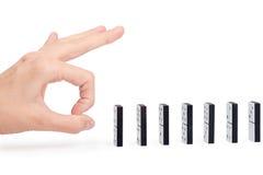 Mano pronta a spingere le parti di domino Fotografie Stock Libere da Diritti