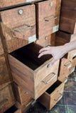 Mano psiquiátrica que abre un cajón del gabinete de madera frecuentado viejo Fotos de archivo libres de regalías