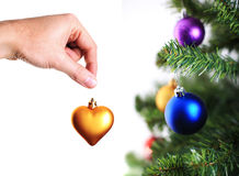 Mano que adorna el árbol de navidad con el corazón del oro Imagenes de archivo