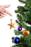 Mano que adorna el árbol de navidad con la estrella de oro Fotografía de archivo libre de regalías