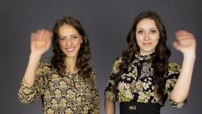 Mano que agita de dos muchachas que dice hola y hola gesto en el fondo dos metrajes