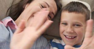 Mano que agita feliz de la madre y del hijo en la cámara metrajes