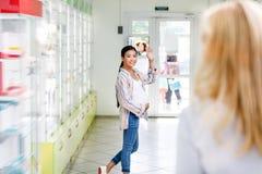 mano que agita sonriente de la mujer embarazada a la situación del farmacéutico Fotografía de archivo libre de regalías