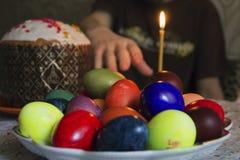 Mano que alcanza para los huevos de Pascua Fotos de archivo