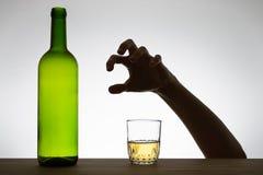 Mano que alcanza para un vidrio de vino Foto de archivo libre de regalías