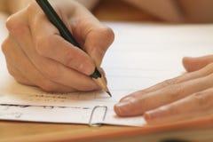 Mano que aprende las letras en clase con el lápiz y el Libro Blanco foto de archivo