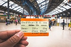 Mano que celebra un boleto de tren BRITÁNICO en Brighton y la estación de tren Hove para el fondo en Brighton, Inglaterra imágenes de archivo libres de regalías