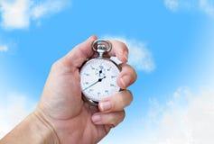 Mano que celebra un cronómetro/un reloj de la producción Fotos de archivo libres de regalías
