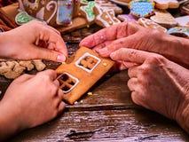 Mano que cocina la casa de pan de jengibre de la Navidad Foto de archivo