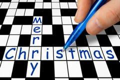 Mano que completa el crucigrama - Feliz Navidad Fotografía de archivo