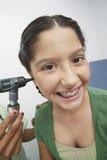 Mano que comprueba el oído de la muchacha feliz con el otoscopio Imagen de archivo