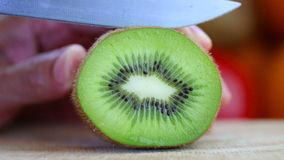 Mano que corta un kiwi con un cuchillo Imagenes de archivo