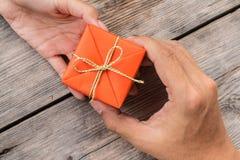 Mano que da la caja de regalo anaranjada y la cinta amarilla Fotos de archivo libres de regalías