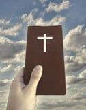Mano que detiene a Christian Book Foto de archivo libre de regalías