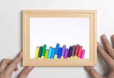Mano que detiene mofa del marco con el lápiz del color para el arte Fotografía de archivo