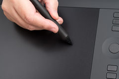 Mano que detiene a Pen Over Table gráfico Imágenes de archivo libres de regalías