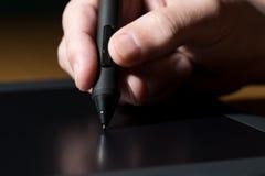 Mano que detiene a Pen Over Table gráfico Imagen de archivo