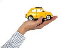 Mano que detiene a Toy Car amarillo Imagenes de archivo