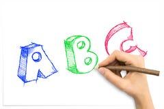 Mano que dibuja las letras incompletas de ABC Foto de archivo