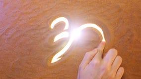 Mano que dibuja símbolo de OM en la arena Seashell de la concha de peregrino en color de rosa Visión superior
