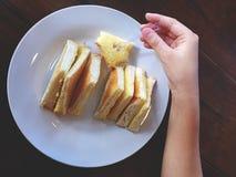 Mano que escoge a Sugar Butter Bread en la placa circular blanca Imagen de archivo libre de regalías