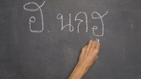 Mano que escribe la letra tailandesa en la pizarra negra metrajes