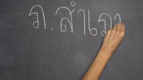 Mano que escribe la letra tailandesa en la pizarra negra almacen de metraje de vídeo