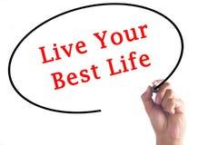 Mano que escribe a Live Your Best Life en tablero transparente imagen de archivo libre de regalías