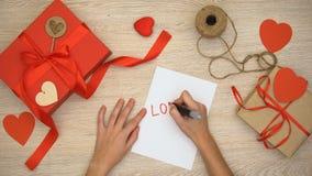 Mano que escribe palabra del amor en el papel, cajas de regalo del arte en el fondo, día de San Valentín almacen de video