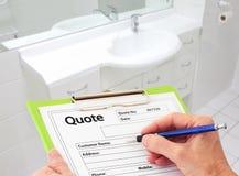Mano que escribe una cotización para la renovación del cuarto de baño foto de archivo