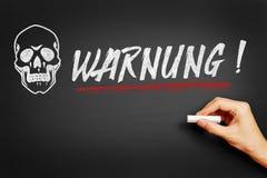 Mano que escribe Warnung Imagenes de archivo