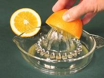 Mano que exprime el zumo de naranja fotos de archivo libres de regalías